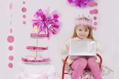 Muchacha con el presente en la fiesta de cumpleaños rosada de la decoración Fotografía de archivo