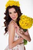 Muchacha con el ramo de flores del narciso y de maquillaje de la moda Fotografía de archivo libre de regalías