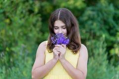 Muchacha con el ramo de flores salvajes azules afuera en verano Foto de archivo