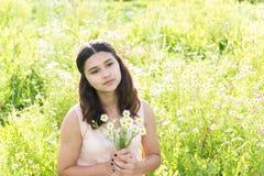 Muchacha con el ramo de margaritas en prado del verano Fotos de archivo libres de regalías
