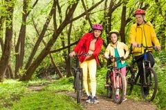 Muchacha con el rastro biking del montaje de los padres que camina Fotos de archivo libres de regalías