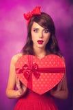 Muchacha con el regalo de la forma del corazón Fotografía de archivo libre de regalías