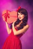 Muchacha con el regalo de la forma del corazón Imagenes de archivo