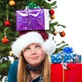 Muchacha con el regalo de la Navidad en la pista que rueda sus ojos Foto de archivo