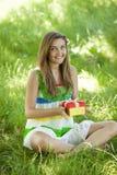 Muchacha con el regalo en el parque en la hierba verde. Fotografía de archivo