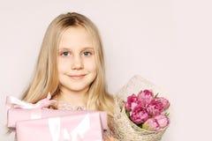 Muchacha con el regalo y las flores Imagenes de archivo