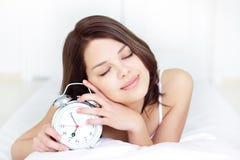 Muchacha con el reloj de alarma Fotos de archivo libres de regalías