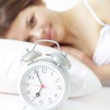 Muchacha con el reloj de alarma Imagen de archivo