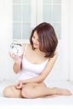 Muchacha con el reloj de alarma Imágenes de archivo libres de regalías