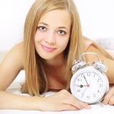 Muchacha con el reloj de alarma Imagen de archivo libre de regalías