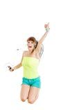 Muchacha con el salto de los auriculares de la alegría que escucha la música Fotografía de archivo libre de regalías