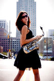 Muchacha con el saxofón en calle fotos de archivo
