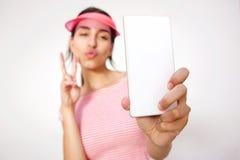 Muchacha con el signo de la paz de la mano que toma el selfie con el teléfono celular Imagen de archivo