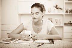 Muchacha con el smartphone que hace la preparación Fotografía de archivo