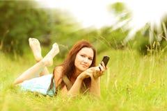 Muchacha con el smartphone que miente en hierba en parque Imagen de archivo libre de regalías