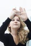 Muchacha con el smartphone que toma un selfie de la foto de sí misma Imagenes de archivo