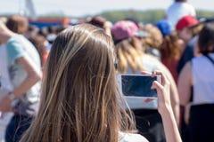 Muchacha con el smartphone, tomando la foto de la muchedumbre Foto de archivo