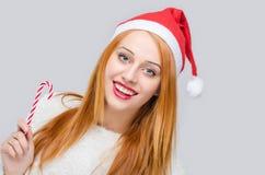 Muchacha con el sombrero de Papá Noel que sonríe sosteniendo un bastón de caramelo Foto de archivo libre de regalías