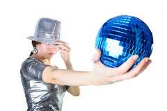 Muchacha con el sombrero de plata que sostiene la bola azul del disco Foto de archivo libre de regalías