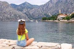 Muchacha con el sombrero del marinero en la bahía de Kotor de las vacaciones de verano Fotos de archivo libres de regalías