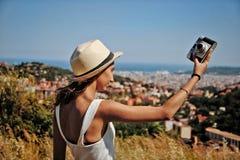 Muchacha con el sombrero que sostiene una cámara imagenes de archivo