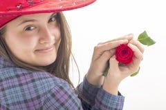 Muchacha con el sombrero rojo que sostiene una rosa roja aislada en blanco Fotos de archivo