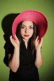 Muchacha con el sombrero rosado en fondo verde Foto de archivo