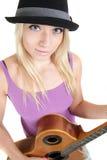 Muchacha con el sombrero, tocando una guitarra acústica Fotos de archivo