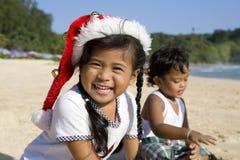 Muchacha con el sombrero y el muchacho de la Navidad en la playa Fotografía de archivo