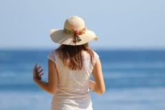 Muchacha con el sombrero y el teléfono celular en la playa Imagenes de archivo