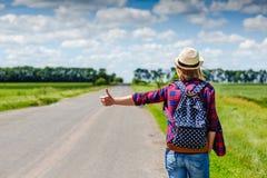 Muchacha con el sombrero y la mochila que hace autostop en el camino imagenes de archivo