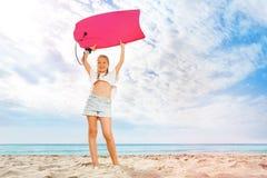 Muchacha con el soporte del tablero del cuerpo en la playa soleada de la arena Imagenes de archivo