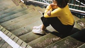 Muchacha con el suéter amarillo de los vidrios que se sienta en el concepto de las escaleras Fotos de archivo