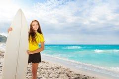 Muchacha con el tablero que practica surf en el mar Foto de archivo libre de regalías