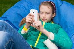Muchacha con el teléfono celular al aire libre en Bean Bag Chair Fotografía de archivo