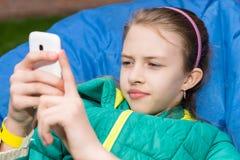 Muchacha con el teléfono celular en Bean Bag Chair azul Fotos de archivo libres de regalías