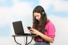 Muchacha con el teléfono celular y el ordenador portátil Fotos de archivo