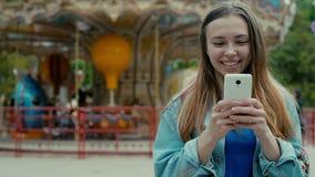 Muchacha con el teléfono contra el contexto de un parque temático almacen de metraje de vídeo
