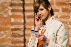 Muchacha con el teléfono de la tarjeta de crédito y móvil Fotografía de archivo