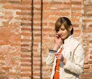 Muchacha con el teléfono de la tarjeta de crédito y móvil Fotografía de archivo libre de regalías