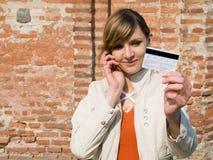 Muchacha con el teléfono de la tarjeta de crédito y móvil Foto de archivo