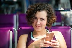 Muchacha con el teléfono a disposición que espera el avión Fotografía de archivo libre de regalías