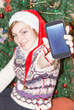 Muchacha con el teléfono elegante en fondo del árbol de navidad Imagen de archivo libre de regalías