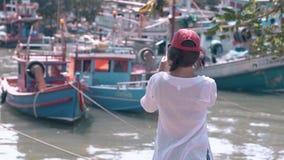 Muchacha con el teléfono en bahía ilustrada con los barcos de pesca el día almacen de video