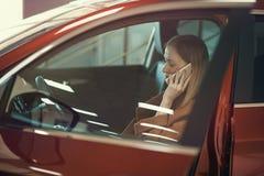 Muchacha con el teléfono en coche Imagen de archivo libre de regalías