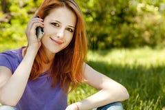 Muchacha con el teléfono móvil en el parque Fotos de archivo libres de regalías