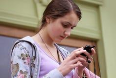 Muchacha con el teléfono móvil en la ciudad Fotos de archivo