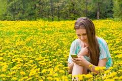 Muchacha con el teléfono móvil en parque Fotos de archivo libres de regalías