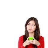 Muchacha con el teléfono móvil que mira para arriba al espacio en blanco Foto de archivo libre de regalías