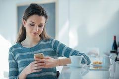 Muchacha con el teléfono móvil que se sienta en el contador de la barra Fotos de archivo libres de regalías